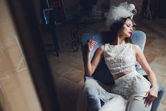 Stilvolle Braut, die im Lehnsessel aufwirft stockbilder