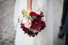 Stilvolle Braut im weißen Kleid der Weinlese, das mit Hochzeitsblumenstrauß aufwirft Lizenzfreies Stockbild