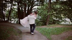 Stilvolle Braut und Bräutigam in einem Park Bräutigam nimmt seine Braut in seinen Armen und in Strudeln herum Glücklicher Liebhab stock footage