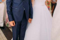 Stilvolle Braut und Bräutigam an ihrem Hochzeitshändchenhalten Lizenzfreie Stockbilder