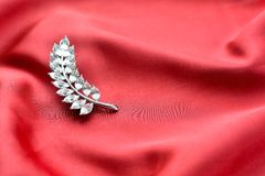 Stilvolle Brosche auf silk Hintergrund Lizenzfreie Stockfotografie