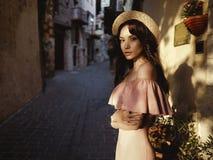 Stilvolle Brunettefrau, die in alte Stadt geht Lizenzfreie Stockbilder