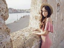 Stilvolle Brunettefrau, die Sonnenaufgang auf Seeseite genießt Stockbilder
