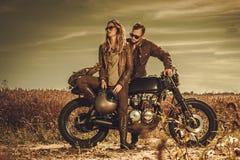 Stilvolle Caférennläuferpaare auf den kundenspezifischen Motorrädern der Weinlese auf einem Gebiet Stockfotos