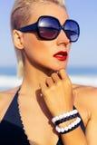 Stilvolle Dame im Urlaub in der modernen Sonnenbrille auf dem Strand Stockfotografie
