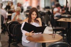 Stilvolle Dame sitzt im Café in der Mitte der Stadt und des Blickes am Menü Sonniges Wetter- und codlgetränk Mädchen in der Sonne stockbilder