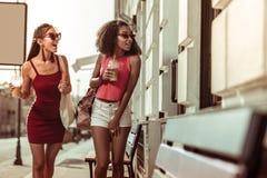 Stilvolle dunkelhaarige gebräunte überraschte ansprechende Damen, welche die Straßen gehen lizenzfreie stockbilder