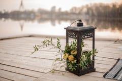 Stilvolle Eisenlaterne verziert mit tropischen Blumen als Hochzeitsdekor auf der Flussbank Stockfotos