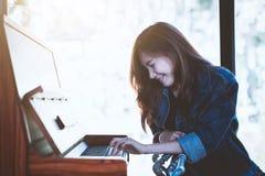 Stilvolle Frau Asien-Schönheit, die ein Retro- Klavier in der Freizeit spielt Stockfoto