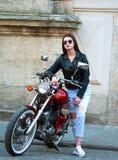Stilvolle Frau in der Lederjacke auf klassischem Motorrad in der Stadt Stockfotografie