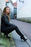 Stilvolle Frau, die auf Wand sich lehnt Stockfotografie