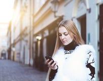 Stilvolle Frau, die ein Telefon simst auf Smartphone verwendet Lizenzfreies Stockfoto