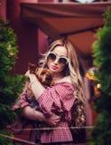 Stilvolle Frau, die einen Hund umarmt stockbild