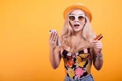 Stilvolle Frau, die Kreditkarte und Telefon hält Lizenzfreies Stockfoto