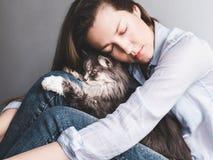 Stilvolle Frau, die leicht Kätzchen umarmt stockfotografie