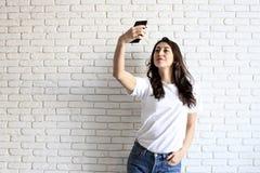 Stilvolle Frau, die selfie mit Einkaufstasche auf dem gelben Wandhintergrund macht Winterurlaubverkauf Lizenzfreie Stockfotografie
