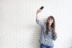 Stilvolle Frau, die selfie mit Einkaufstasche auf dem gelben Wandhintergrund macht Winterurlaubverkauf Lizenzfreies Stockbild
