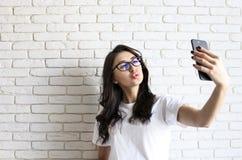 Stilvolle Frau, die selfie mit Einkaufstasche auf dem gelben Wandhintergrund macht Winterurlaubverkauf Stockbild