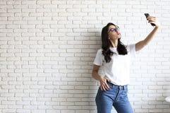 Stilvolle Frau, die selfie mit Einkaufstasche auf dem gelben Wandhintergrund macht Winterurlaubverkauf Lizenzfreie Stockfotos