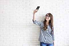Stilvolle Frau, die selfie mit Einkaufstasche auf dem gelben Wandhintergrund macht Winterurlaubverkauf Stockfotos