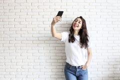 Stilvolle Frau, die selfie mit Einkaufstasche auf dem gelben Wandhintergrund macht Winterurlaubverkauf Stockbilder