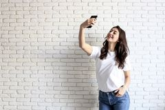 Stilvolle Frau, die selfie mit Einkaufstasche auf dem gelben Wandhintergrund macht Winterurlaubverkauf Lizenzfreie Stockbilder
