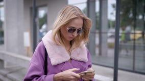 Stilvolle Frau, die Smartphone auf Straße verwendet stock video