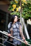 Stilvolle Frau, die in die Stadt in der städtischen Straßenart der Pelz-Weste, Modetrend geht stockbild