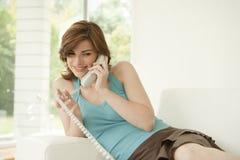 Stilvolle Frau, die zu Hause das Telefon verwendet Stockbild