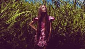 Stilvolle Frau im rosa Kleid im Dickicht Stockfotografie
