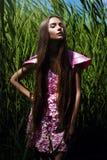 Stilvolle Frau im rosa Kleid im Gras Stockbilder