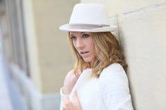 Stilvolle Frau mit dem Hut, der auf der Wand sich lehnt Lizenzfreie Stockfotografie