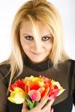 Stilvolle Frau mit den roten und gelben Tulpen Lizenzfreie Stockfotos