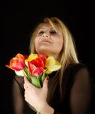 Stilvolle Frau mit den roten und gelben Tulpen Stockbild