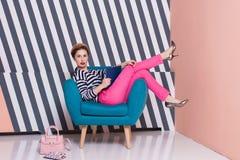 Stilvolle Frau mit einem Laptop in ihren Händen in einem gestreiften T-Shirt und in rosa Hosen, Lebensstil, Blogger, Geschäft Lizenzfreies Stockfoto