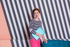 Stilvolle Frau mit einem Laptop in ihren Händen in einem gestreiften T-Shirt und in rosa Hosen, Lebensstil, Blogger, Geschäft Lizenzfreies Stockbild