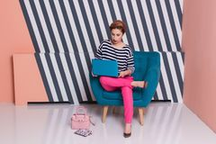 Stilvolle Frau mit einem Laptop in ihren Händen in einem gestreiften T-Shirt und in rosa Hosen, Lebensstil, Blogger, Geschäft Lizenzfreie Stockbilder