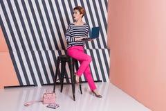 Stilvolle Frau mit einem Laptop in ihren Händen in einem gestreiften T-Shirt und in rosa Hosen, Lebensstil, Blogger, Geschäft Stockbilder