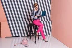 Stilvolle Frau mit einem Laptop in ihren Händen in einem gestreiften T-Shirt und in rosa Hosen, Lebensstil, Blogger, Geschäft Lizenzfreie Stockfotografie