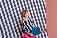 Stilvolle Frau mit einem Laptop in ihren Händen in einem gestreiften T-Shirt und in rosa Hosen, Lebensstil, Blogger, Geschäft Stockfoto