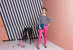 Stilvolle Frau mit einem Laptop in ihren Händen in einem gestreiften T-Shirt und in rosa Hosen, Lebensstil, Blogger, Geschäft Lizenzfreie Stockfotos