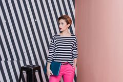 Stilvolle Frau mit einem Laptop in ihren Händen in einem gestreiften T-Shirt und in rosa Hosen, Lebensstil, Blogger, Geschäft Stockfotografie