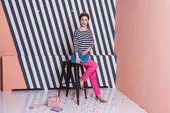 Stilvolle Frau mit einem Laptop in ihren Händen in einem gestreiften T-Shirt und in rosa Hosen, Lebensstil, Blogger, Geschäft Stockfotos