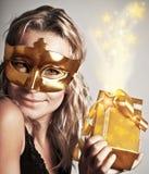 Stilvolle Frau mit goldener Schablone und Geschenk Stockfotos