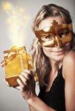 Stilvolle Frau mit goldener Schablone und Geschenk Stockfoto