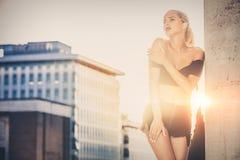 Stilvolle Frau mit städtischem Sonnenuntergang hinten Zufällige Kleidung, blondes Haar und sinnliche Haltung stockfotos