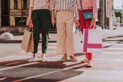 Stilvolle Frauen halten Einkaufstaschen im Freien stockfotos