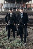 Stilvolle Gangstermänner, werfend auf Hintergrund der Eisenbahn auf Thema Englands im Jahre 1920 s moderne grobe überzeugte Grupp Lizenzfreie Stockfotos