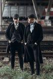 Stilvolle Gangstermänner, werfend auf Hintergrund der Eisenbahn auf Thema Englands im Jahre 1920 s moderne grobe überzeugte Grupp Lizenzfreies Stockfoto