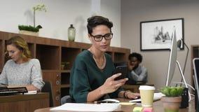 Stilvolle Geschäftsfrau unter Verwendung des Smartphone stock footage